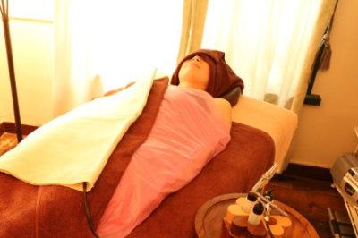 パラフィンシート、タオルで全身を温め、発汗している写真